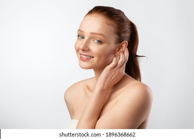 Haircare. Ginger-Haired Young Woman With Ponytail Hairstyle Posing Touching Smooth Red Hair Standing In Studio Over White Background, Smiling To Camera. Youth, Female Beauty Portrait Concept