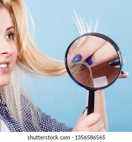 Haircare and hairstyling, bad effects of bleaching concept. Happy blonde woman looking at her damaged, split hair ends through magnifying glass.