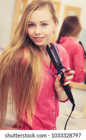Haircare and hairstyling concept. Woman having fun while straightening her long blond hair using straightener tool.