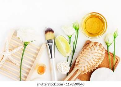 Haircare natural products, essential oils & herbal extract, brush, top view white table ingredients beauty treatment.
