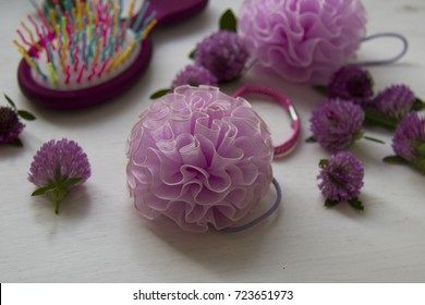 Haircare objects and fresh clover flowers over the whte background