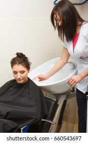 Haircare, relaxation and hairstyling concept. Woman sitting in black cape getting her hair washed by hairdresser