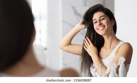 Haircare. Smiling Girl Touching Hair Looking In Mirror In Bathroom. Panorama, Selective Focus