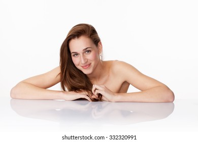 haircare and wellbeing concept - happy 20s woman with long brown hair smiling leaning on clear white glass at beauty spa,studio shot