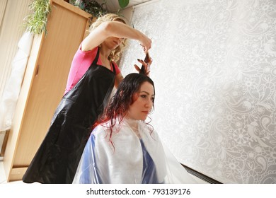 Haircut being made by hairdresser for young caucasian woman with dyed hair. Horizontal shot