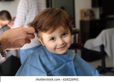 haircut of a happy little kid in the barbershop