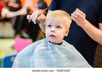 Haircut for a little boy. The boy sits at the hairdresser. Wet hair on the head, haircut and styling.