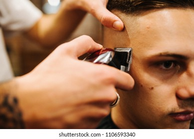 Haircut men barbershop. Pleasant barber using grooming professional haircutting machine to making haircut to client close up. Man haircut. Soft focus.
