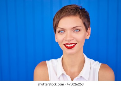 Haircut and red lipstick make up. Colorful portrait of smiling young woman. Blue background.