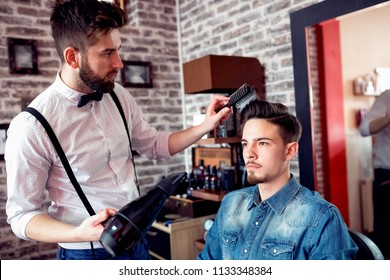 Hairdresser adjusts hair a customer with a comb and hairdryer