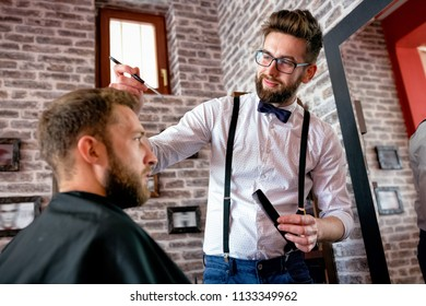 Hairdresser adjusts hair a customer with a comb in barbershop salon