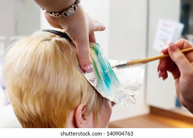 hairdresser applying hair color in a salon
