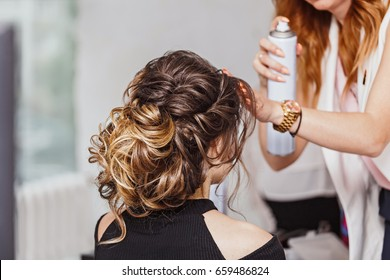 Hairdresser applying hair spray on brunette hair in beauty salon