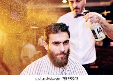 Hairdresser or barber sprinkles water on the client's hair in modern barbershop