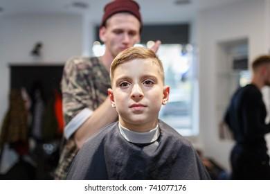 Hairdresser barbershop parihopher strechot small boy sitting on a chair