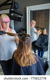Hairdresser with black gloves combing hair of beautiful young woman in the process of hair color change