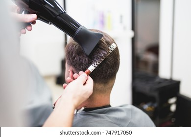 Hairdresser blow drying his client's hair. Selective focus.