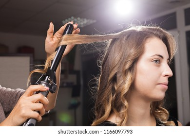 hairdresser carefully making hairculing to a beautiful client in a beauty salon at a master class. concept of professional stylists studying