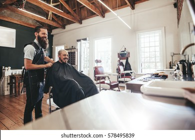 Hairdresser with client sitting at salon and smiling. Man getting haircut at barber shop.
