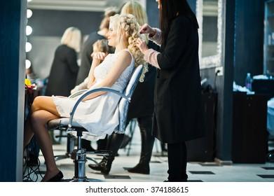 Hairdresser coiffeur makes hairstyle of gentle blonde bride