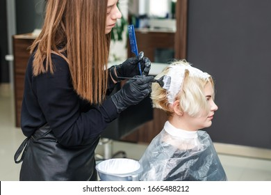 Hairdresser colors hair of woman with white dye in beauty salon.
