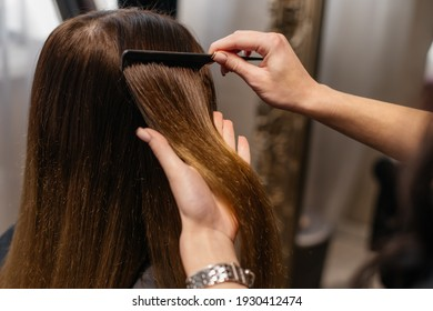 The hairdresser is combing the hair of the client. Close-up of hands with a comb and client's hair.