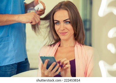 Hairdresser combing hair woman with mobile phone in hairdressing salon. Concept of fashion and beauty. Positive emotion