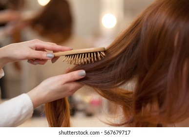 Hairdresser combing her long, red hair of his client in the beauty salon. Professional hair care and creating hairstyles.