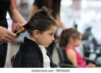 Hairdresser combing little girl hair in beauty center
