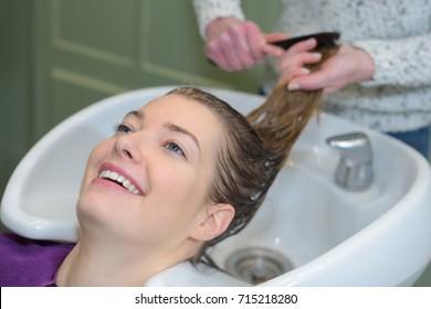 Hairdresser combing wet hair over sink