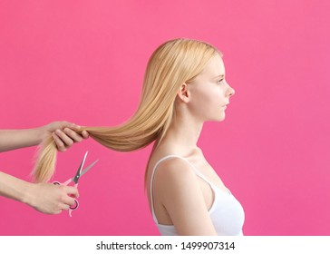 Hairdresser Concept photo Woman's hand is cutting off the long hair of the blonde girl against pink background