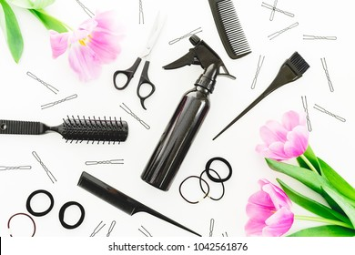 Hairdresser concept with spray, scissors, combs, barrette and tulips flowers on white background. Beauty concept. Flat lay, top view
