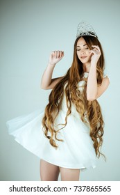 Hairdresser and cosmetics. Beauty salon and wedding fashion. Girl has fashionable makeup and healthy hair on grey background. Haircare and prom queen. Woman with long hair white dress and crown.