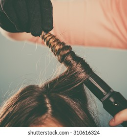 Hairdresser curling woman hair with electric iron curler tong. Hairstylist making girl hairstyle. Beauty. Instagram filter.