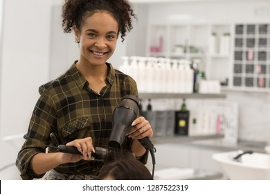 Hairdresser with curly hair holding hair dryer and brush in hands. Young happy girl in checkered shirt looking at camera and smiling. Professional hair cutter making coiffure in beauty salon.