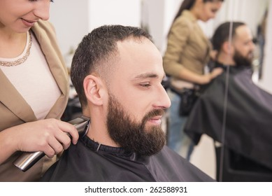 Hairdresser cuting hair with hair clipper on back of the head  in hairdressing salon