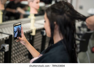 Hairdresser cuts and comb young womans hair while looking phone