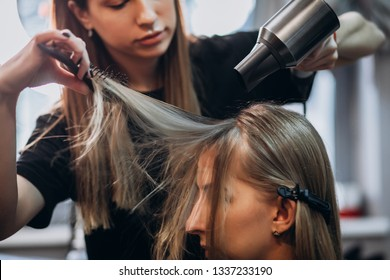 Hairdresser cuts hair by scissors beautiful blonde girl