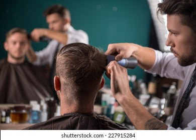 hairdresser  cuts    hair  with hair clipper on back of the head of handsome satisfied  client in  professional  hairdressing salon