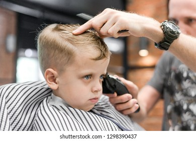 Hairdresser cuts hair little boy blonde with blue eyes making a fashionable hairstyle clipper close-up