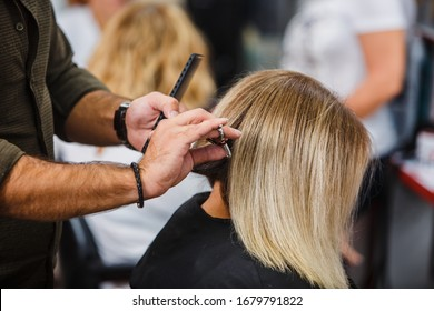hairdresser cuts hair with scissors on crown satisfied client in professional hairdressing salon