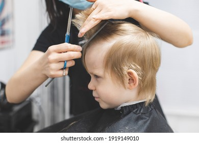 Hairdresser cuts hair serious strict blond child boy. Lifestyle close-up. Concept of beauty, hygiene.