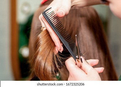 Hairdresser cuts hair of woman close up in beauty salon.