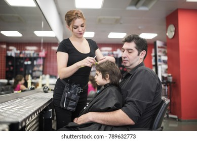 Hairdresser cuts little baby hair with fathers help