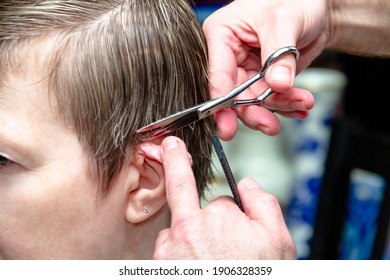 The hairdresser cuts a young woman with scissors.