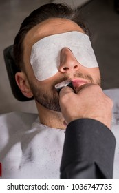 Hairdresser cutting the beard to a client with an electric machine