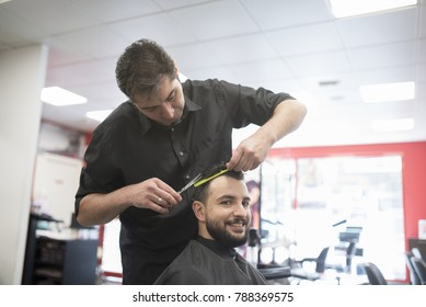 Hairdresser cutting bearded man hair