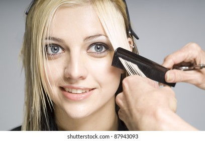 Hairdresser cutting client or customer with comb
