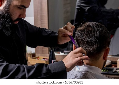 Hairdresser cutting a client's hair with a razor