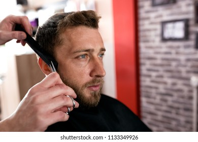 Hairdresser cutting a client's hair with scissors and makes a haircut
